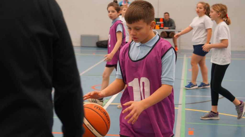 child playing basketball at three hills sports park
