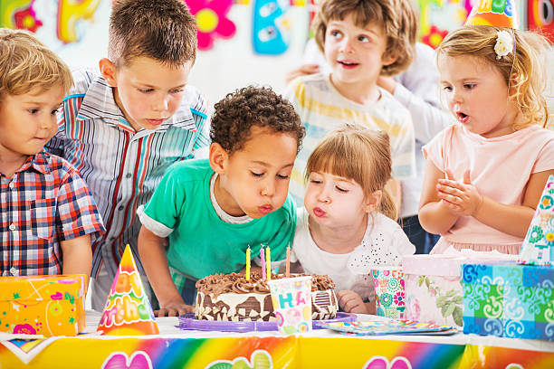 Children on a birthday party blowing birthday candles.